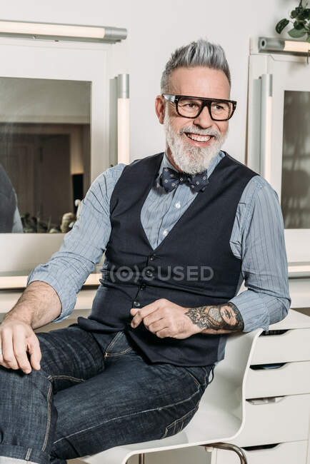 Trendy mature hipster businessman in eyewear and trendy clothes looking away and smiling on chair in house — Stock Photo