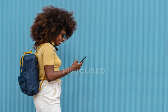Black woman with afro hair listening to music on mobile in front of a blue wall — Stock Photo