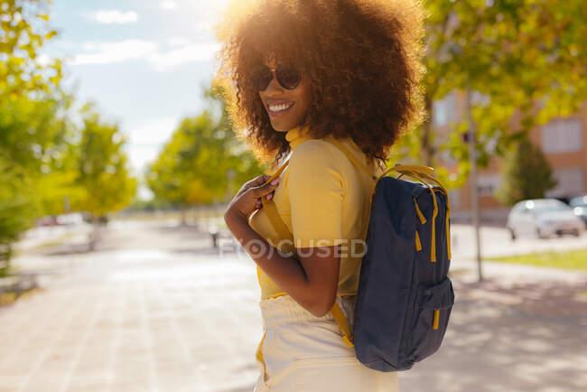 Schwarze Frau mit lockigem Haar läuft die Straße hinunter und lacht glücklich — Stockfoto