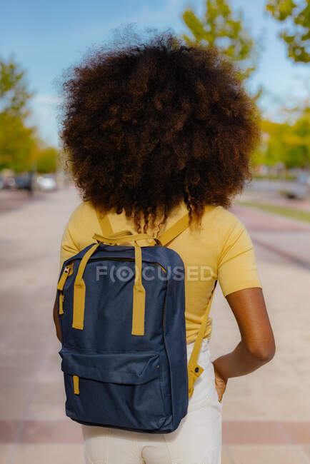 Back view black woman with afro hair with a backpack on her back — Stock Photo