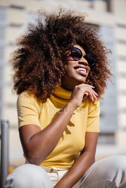 Чорна жінка з кучерявим волоссям сидить на стіні на вулиці і весело сміється — стокове фото