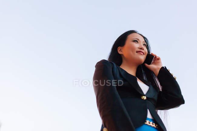 D'en bas de l'entrepreneure asiatique dans un style décontracté intelligent debout dans la rue du centre-ville et parlant sur un téléphone mobile tout en regardant loin — Photo de stock