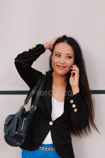 Contenido Empresaria asiática hablando en smartphone mientras discute un proyecto empresarial y mira hacia otro lado — Stock Photo