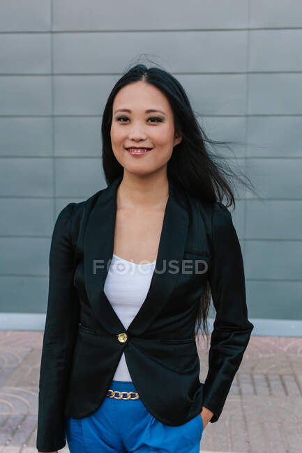 Vista laterale dell'imprenditrice asiatica sicura di sé camminando lungo la strada vicino all'edificio urbano e guardando altrove — Foto stock