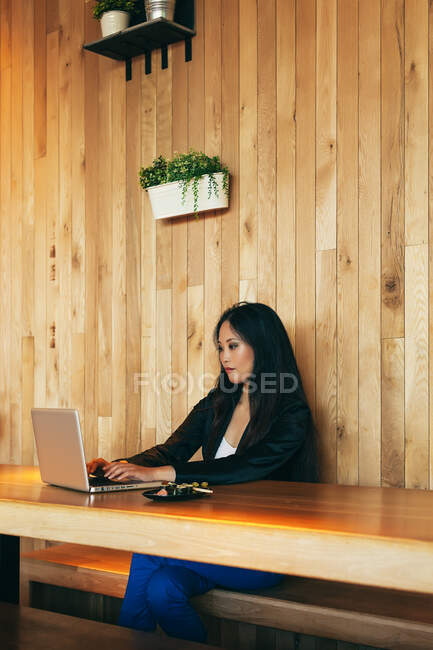 Focused Asian female entrepreneur sitting at table in cafe and typing on netbook while working on online project remotely — Stock Photo