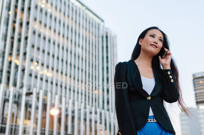 Low angle of Asian female entrepreneur standing in street of megalopolis and speaking on mobile phone while discussing business issues and looking away — Stock Photo