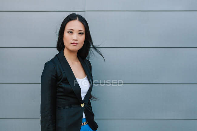 Self confident Asian female entrepreneur standing on the street near urban building and looking at camera — Stock Photo