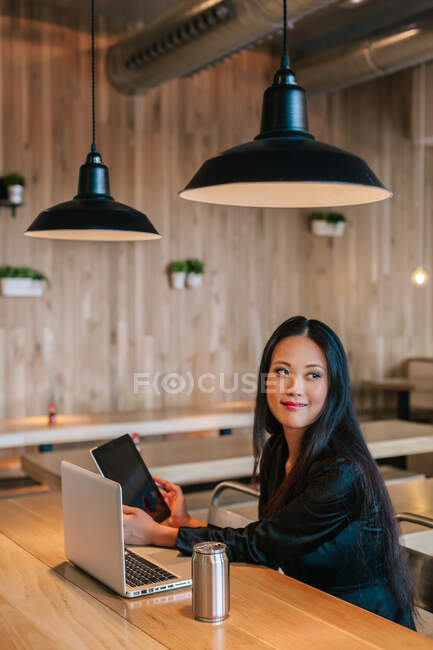 Content ethnic female entrepreneur sitting at table with tablet and laptop while working on project and looking away — Stock Photo