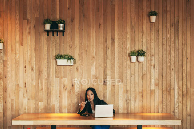 Busy Asian female entrepreneur sitting at table in cafe while eating sushi and working on remote project via netbook — Stock Photo