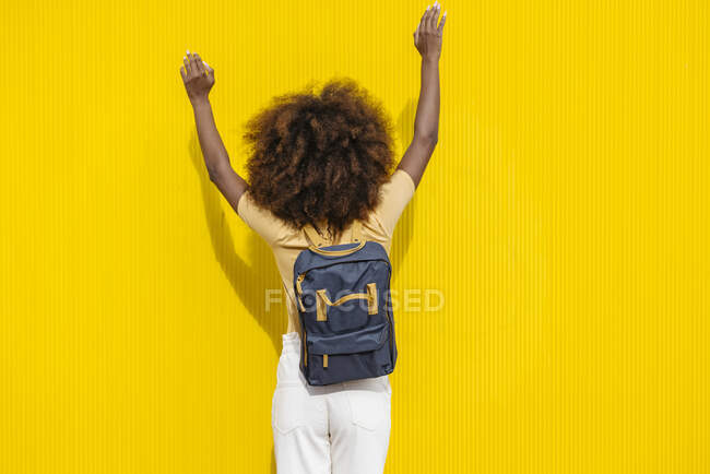 Back view ethnic female with Afro hairstyle raised arms while on yellow background in sunlight — Stock Photo