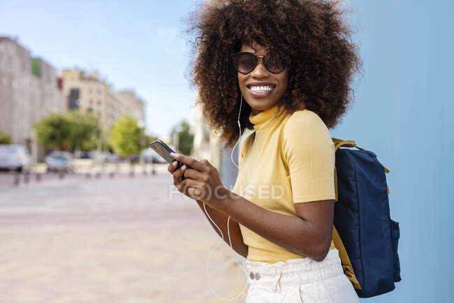 Content young ethnic female in sunglasses with Afro hairstyle browsing internet on cellphone while listening to music on street — Fotografia de Stock