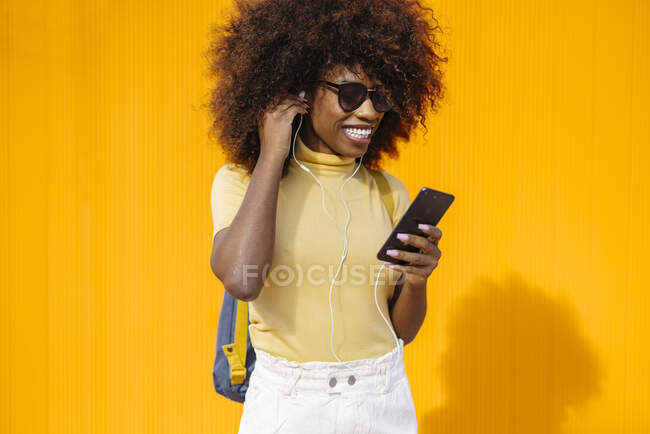 Zufriedene junge ethnische Frau mit Sonnenbrille und Afro-Frisur surft im Internet auf dem Handy, während sie Musik auf gelbem Hintergrund hört — Stockfoto