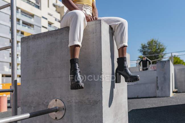 Cultivo afroamericano mujer en ropa casual sentado en la fachada en la calle - foto de stock