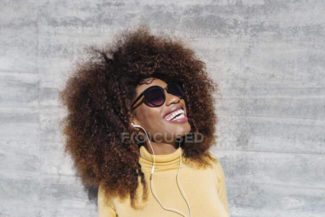Молода етнічна жінка з африканською зачіскою, яка слухає музику і сміється на сонці біля сірої стіни. — стокове фото