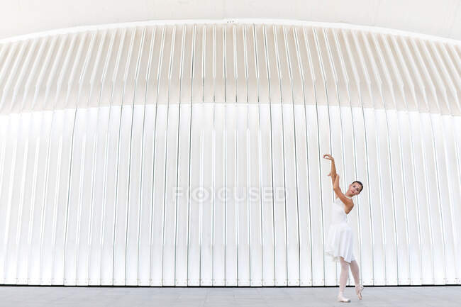 Young female ballet dancer in pointe shoes with raised leg and arm dancing on tiled pavement outdoors looking at camera — Stock Photo