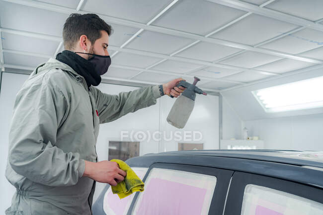 Бічний вид робітника в масці і одноманітний фарбування автомобіля при використанні фарби пістолет — стокове фото