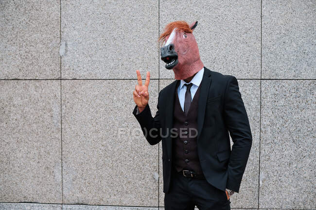 Anonymous male entrepreneur wearing rubber horse mask and formal suit standing on street in city and showing two fingers — Stock Photo