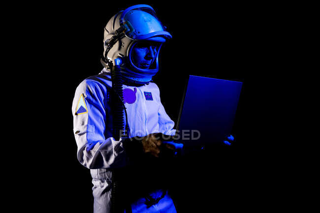 Concentrated astronaut in spacesuit and helmet browsing modern netbook while standing on black background — Stock Photo