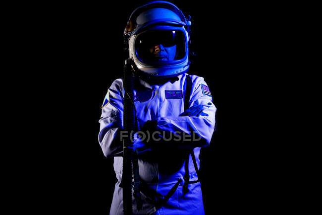 Male cosmonaut wearing white space suit and helmet while standing on black background in blue neon light — Stock Photo