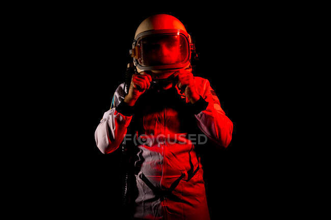 Male cosmonaut wearing white space suit and helmet while standing on black background in red neon light — Stock Photo