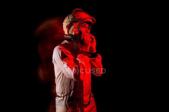 Side view of male cosmonaut wearing white space suit and helmet while standing on black background in red neon light looking away — Stock Photo