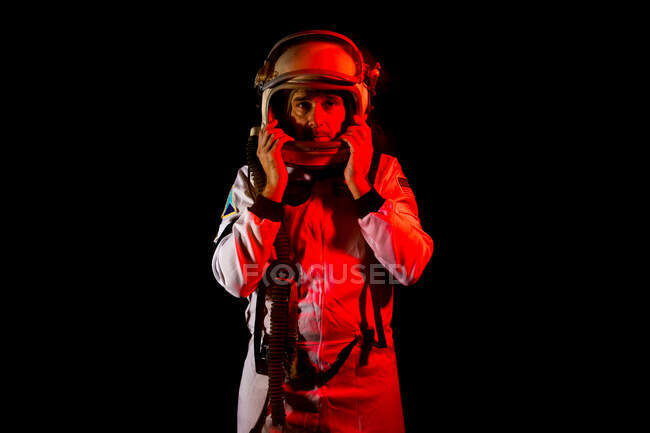 Male cosmonaut wearing white space suit and helmet while standing on black background in red neon light looking at camera — Stock Photo