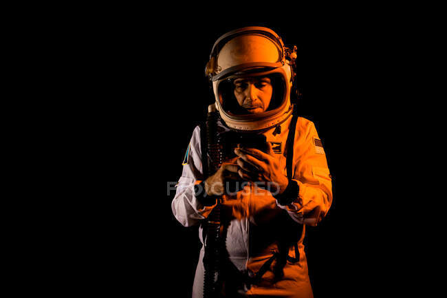Contemplative male cosmonaut in white spacesuit and helmet browsing modern smartphone while standing on black background — Stock Photo