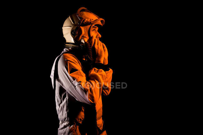 Side view of male cosmonaut wearing white space suit and helmet while standing on black background in orange neon light looking away — Stock Photo