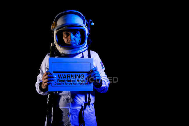 Serious adult male cosmonaut in spacesuit and helmet demonstrating placard with text Warning Restricted Area Deadly Force Authorized while standing on black background and looking at camera — Stock Photo