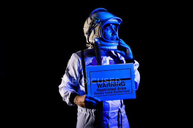 Serious adult male cosmonaut in spacesuit and helmet demonstrating placard with text Warning Restricted Area Deadly Force Authorized while standing on black background and looking away — Stock Photo