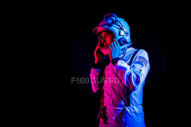 Side view of male cosmonaut wearing white space suit and helmet while standing on black background in purple neon light looking away — Stock Photo