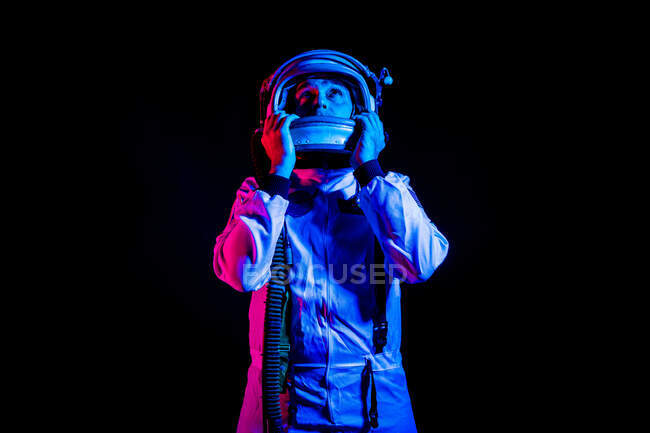 Male cosmonaut wearing white space suit and helmet while standing on black background in pink and blue neon light looking away — Stock Photo