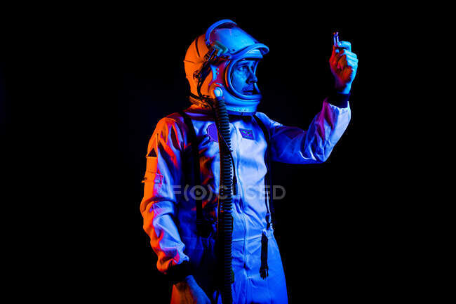 Serious male cosmonaut in spacesuit and helmet looking at vaccine vial in raised hand while standing on black background in blue neon light — Stock Photo