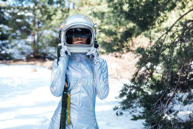 Astronauta joven e irreconocible enfocada en traje espacial y casco de pie en un bosque nevado - foto de stock