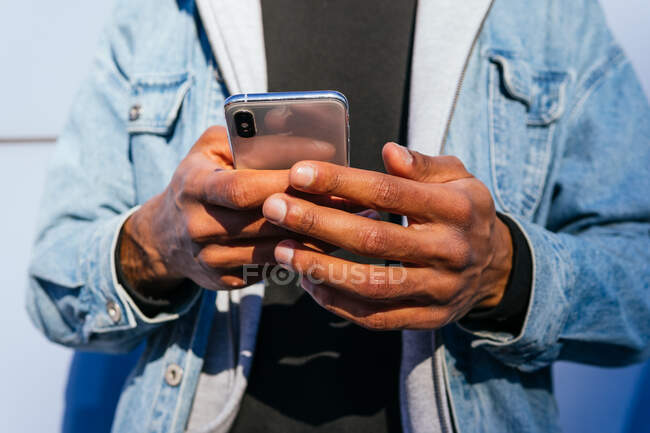 Cropped unrecognizable adult ethnic male in casual wear using mobile phone while standing on the street — Stock Photo