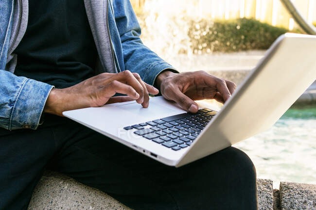 Cropped unrecognizable ethnic African american adult male remote employee with laptop sitting in city — Stock Photo