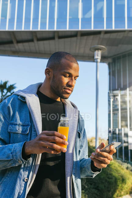 Adult ethnic African American male with bottle of orange juice surfing internet on cellphone in city — Photo de stock