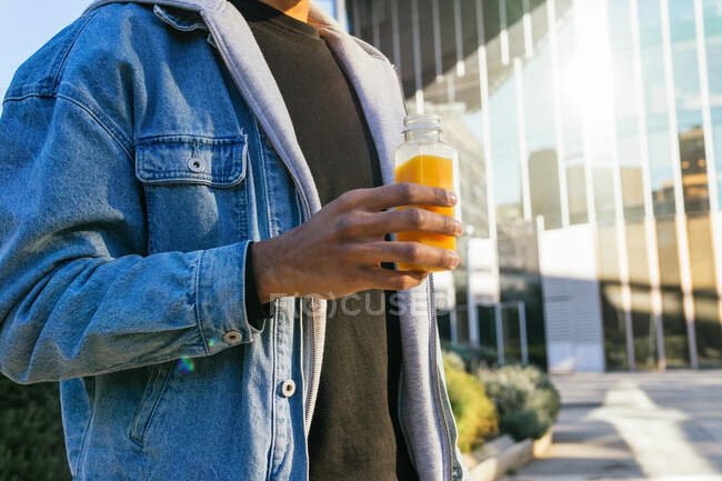 Cropped unrecognizable adult African American male enjoying tasty orange juice from bottle while standing in town — Stock Photo
