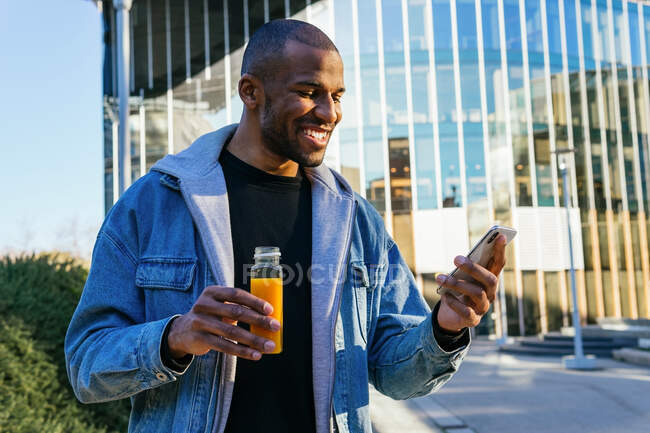 Content adult African American male with bottle of orange juice surfing internet on cellphone in city — Photo de stock
