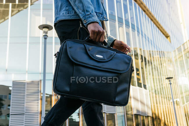 From below cropped unrecognizable adult ethnic male in casual outfit with leather briefcase strolling in town — Stock Photo