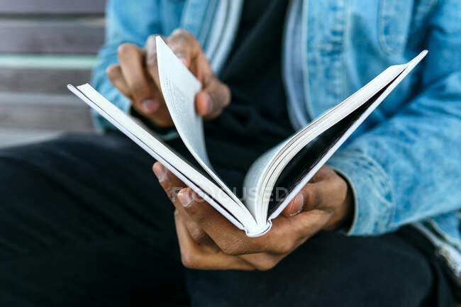 Cultivado irreconocible adulto étnico masculino en ropa casual diario de lectura mientras está sentado en la calle urbana - foto de stock