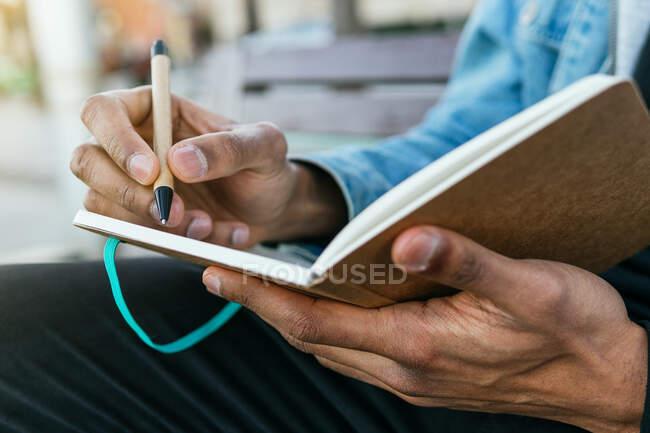 Cultivado irreconocible adulto étnico masculino en ropa casual con un per escritura en el diario mientras está sentado en la calle urbana - foto de stock