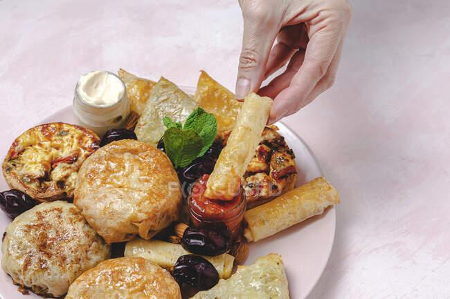 Desde arriba de la cosecha irreconocible persona con apetitosa comida árabe y salsa de tomate en frasco durante las vacaciones de Ramadán - foto de stock