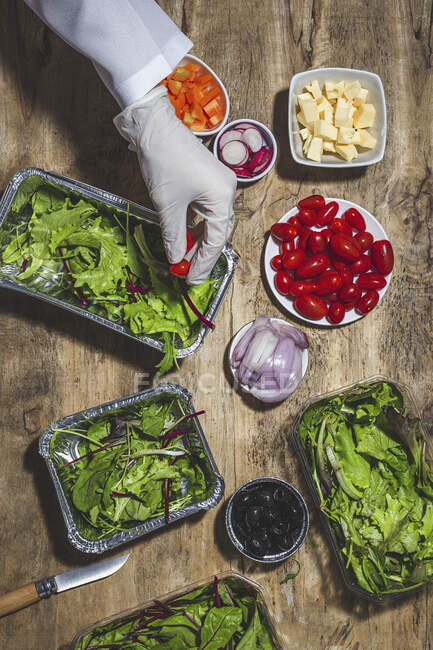 From above crop anonymous professional chef in glove adding ripe red cherry tomatoes to fresh mixed leaves in foil bowl placed on table near salad vegetable ingredients — Fotografia de Stock