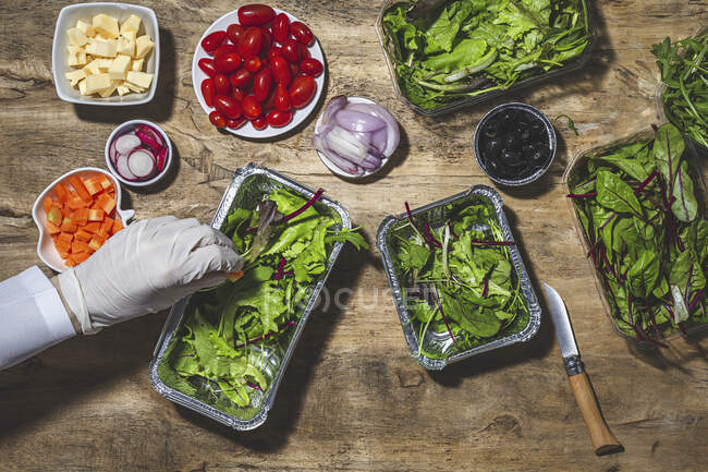 From above crop anonymous professional chef in glove adding carrot slices in foil bowl placed on table near salad vegetable ingredients — Stock Photo