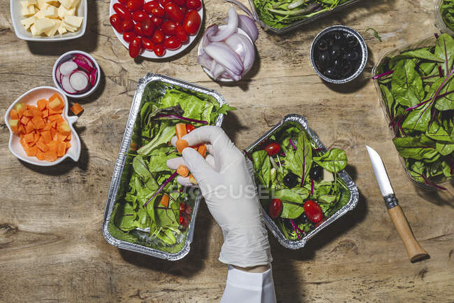 From above crop anonymous professional chef in glove adding carrot slices in foil bowl placed on table near salad vegetable ingredients — Fotografia de Stock