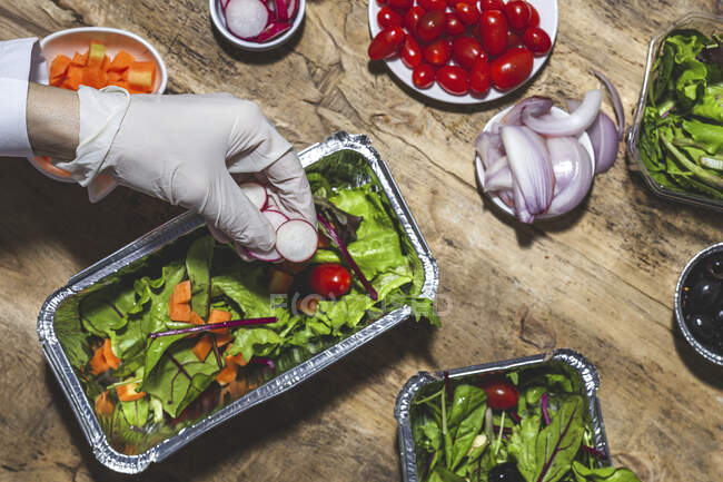 From above crop anonymous professional chef in glove adding onion slices to fresh mixed leaves in foil bowl placed on table near salad vegetable ingredients — Fotografia de Stock