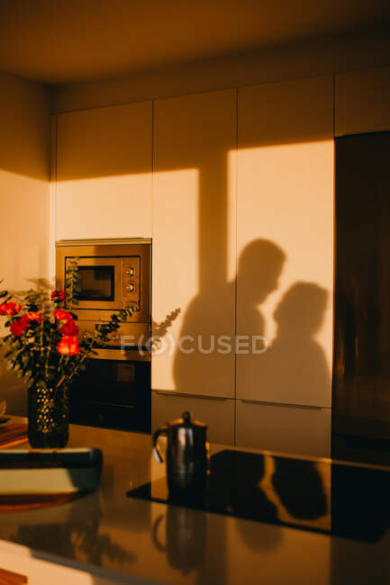 Shadow of unrecognizable couple standing together in cozy kitchen in house in dusk light — Stock Photo