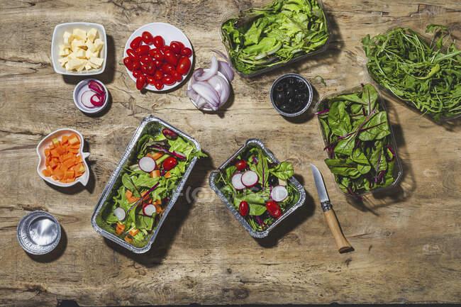 Состав из вкусных овощных салатов в фольге, размещенных на столе рядом с различными ингредиентами, в том числе помидоры черри лук редис и морковь — стоковое фото
