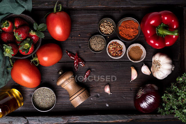 Top view of fresh ripe tomatoes and strawberry placed on wooden table with various spices and ingredients for Gazpacho soup recipe — Stock Photo